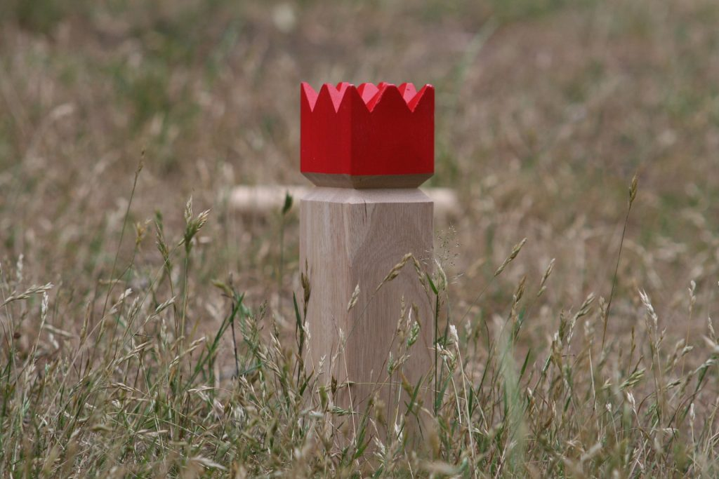 Kubb King piece standing upright within a field of grass.